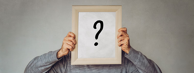 Man holding an empty frame with a question mark